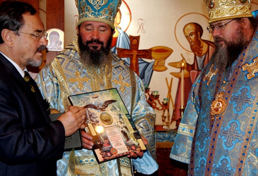 "Valerie Balakirev [left], representing the ""National Awards Committee"" of Russia, presents the ""Triumph of Orthodoxy"" Award to Metropolitan Jonah [right], as Archbishop Justinian looks on."