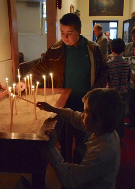 Boys lighting candles